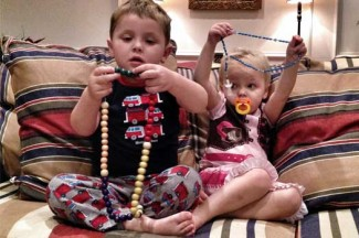 """The author's son Benedict """"teaching"""" his sister Rita the rosary."""