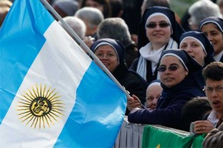 A nun holds Argentina's flag as pilgrims wait for Palm Sunday Mass in St. Peter's Square. (CNS photo/Paul Haring)