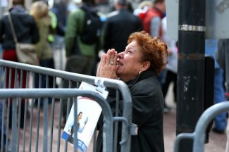A woman prays at the site of explosions at the Boston Marathon.