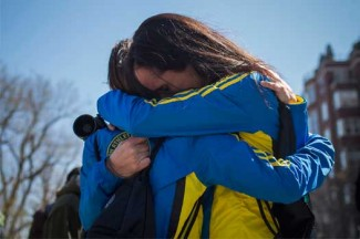 Boston Marathon runners embrace at the barricaded entrance near the finish line. (CNS photo/Shannon Stapleton, Reuters)