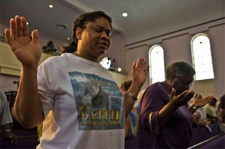 Women pray during a service at the New Life Word Center Church in Sanford, Fla., after the George Zimmerman murder trial. (CNS photo/Steve Nesius, Reuters)