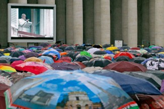 People shelter from rain as Pope Francis leads a devotion at the Vatican. (CNS photo/Giampiero Sposito, Reuters)