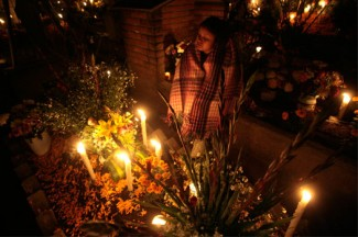 """A woman stands near the grave of a relative in Mexico City to celebrate the """"Day of the Dead."""" (CNS photo)"""