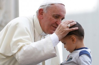 Pope Francis blesses a boy as he leaves his general audience in St. Peter's Square. (CNS photo/Paul Haring)