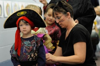 A teacher helps a student with his costume during a Halloween party. (CNS photo/Mike Crupi, Catholic Courier)