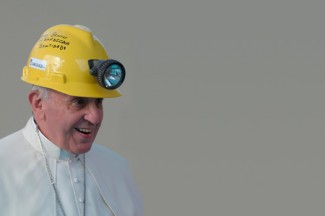 Pope Francis wears a hard hat he received from a miner during Mass the outside Shrine of Our Lady of Bonaria in Sardinia. (CNS photo/L'Osservatore Romano via Reuters)