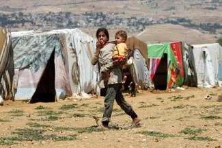 A girl carries her younger brother across a refugee camp in Lebanon. (CNS photo/Sam Tarling, Catholic Relief Services)