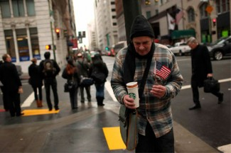 A man panhandling holds an American flag in San Francisco's financial district. (CNS photo/Robert Galbraith, Reuters)