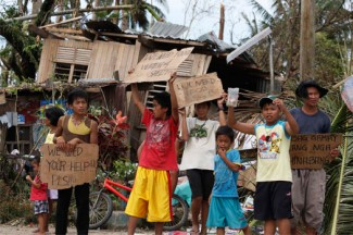 Young people hold signs asking for help after Typhoon Haiyan hits the Philippines. (CNS photo/Charlie Saceda, Reuters)