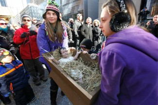Young women carry a crib containing the Christ child to the creche at Daley Plaza in Chicago. (CNS photo/Karen Callaway, Catholic New World)