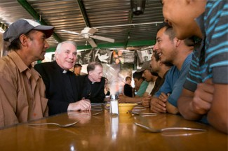 Father Clete Kiley and Bishop John C. Wester of Salt Lake City talk with men at the Aid Center for Deported Migrants in Nogales, Mexico. (CNS photo/Nancy Wiechec)