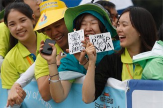 Young women wait for Pope Francis to arrive to celebrate the closing Mass of the Asian Youth Day at Haemi Castle in Haemi, South Korea. (CNS photo/Paul Haring)