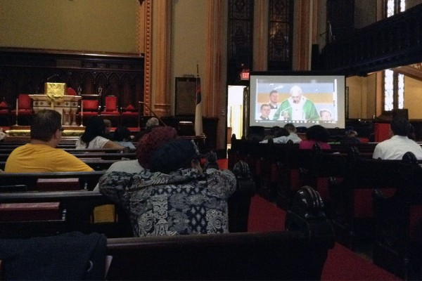 Diners at Grace Cafe watch Pope Francis saying Mass inside the sanctuary of Arch Street United Methodist Church. Photo by Barbara Wheeler-Bride