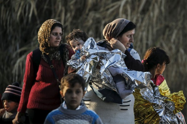 A Syrian refugee carries her child in a thermal blanket as refugees and migrants arrive on an overcrowded boat on the Greek island of Lesbos. (CNS photo/Alkis Konstantinidis, Reuters)