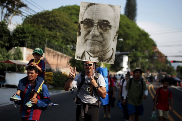 A pilgrim carries a poster of Archbishop Oscar Romero at El Salvador del Mundo Square. (CNS photo/Jose Cabezas, Reuters)