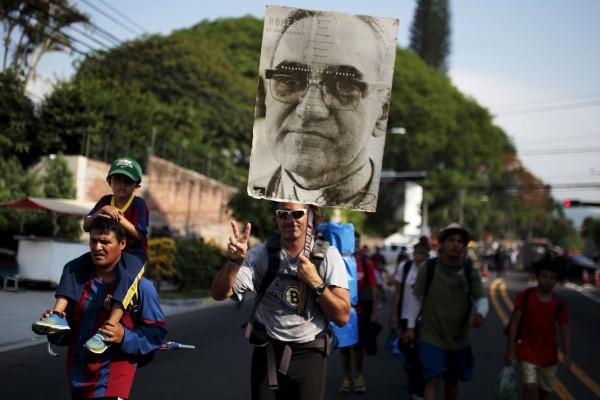 A pilgrim carries a poster of Archbishop Oscar Romero at El Salvador del Mundo Square. (CNS photo/Jose Cabezas, Reuters)