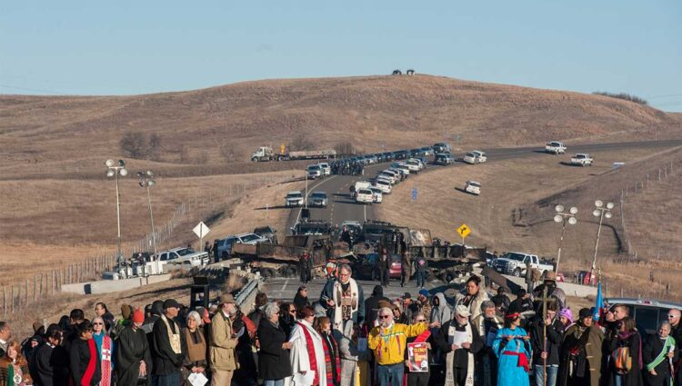 A prayer circle in front of a bridge in Standing Rock, N.D., where demonstrators confront police during a protest of the Dakota Access pipeline. (CNS photo/Stephanie Keith, Reuters)