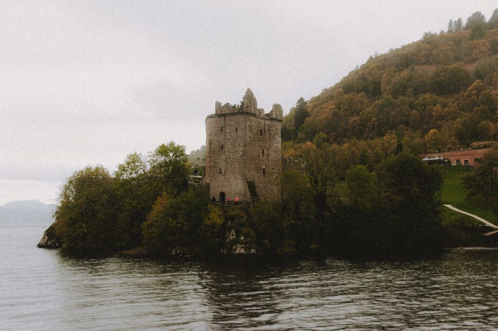 A medieval looking tower in the middle of a marshy lake.