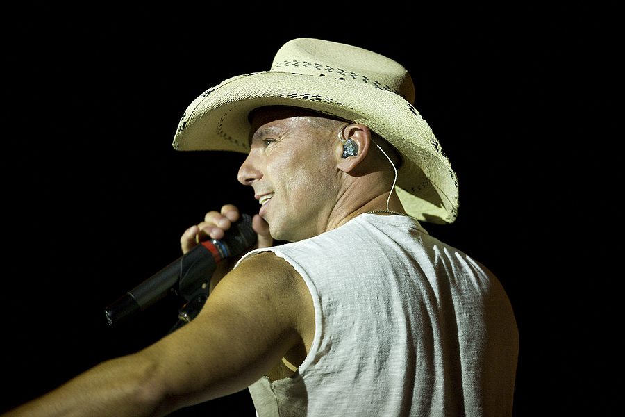 Kenny Chesney wearing a coyboy hat singing into a microphone