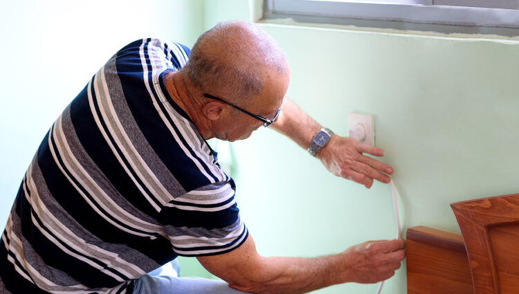 for an article about Alzheimer's, a man measures a wall as for repairing
