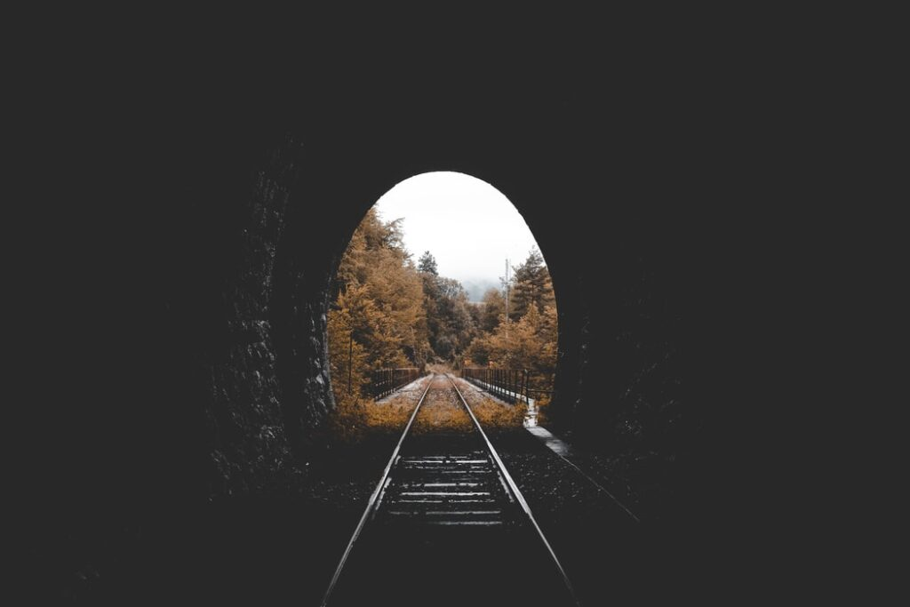 A dark tunnel with train tracks through it and trees on the other side.